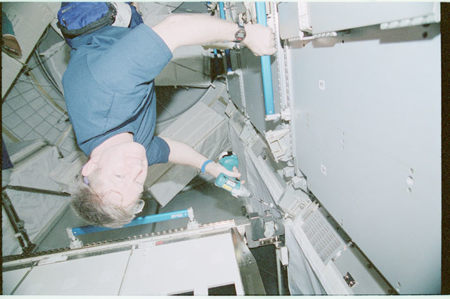 STS102-368-025 - STS-102 - Shepherd uses power tool to remove rack restraining bolts