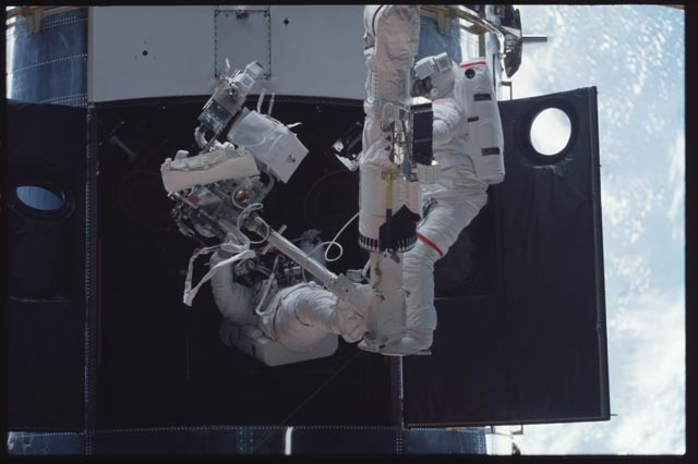 STS103-331-013 - STS-103 - 1st EVA - MS Smith and Grunsfeld during RSU changeout