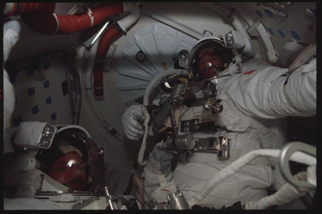 STS103-340-027 - STS-103 - MS Grunsfeld and Smith in their EMUs in the airlock