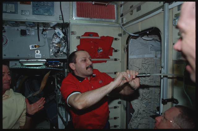 STS105-306-018 - STS-105 - Usachev shoots water from a dispenser into his mouth
