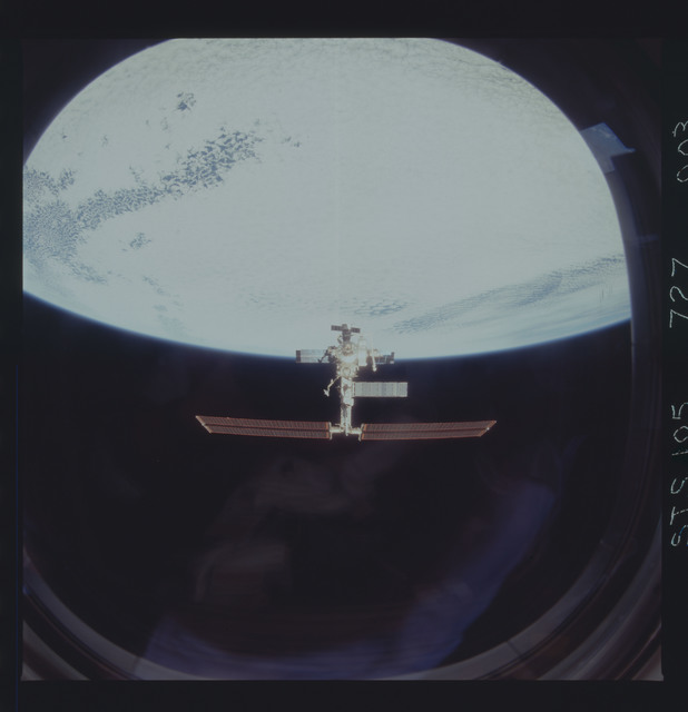 STS105-727-003 - STS-105 - Flyaround documentation of the ISS over the Earth limb after undocking