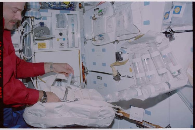 STS106-351-008 - STS-106 - Pilot Altman unpacks a stowage bag on the middeck during STS-106