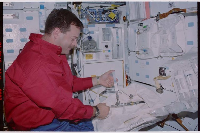 STS106-351-009 - STS-106 - Pilot Altman unpacks a stowage bag on the middeck during STS-106