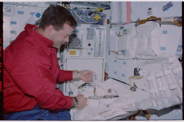STS106-351-010 - STS-106 - Pilot Altman unpacks a stowage bag on the middeck during STS-106