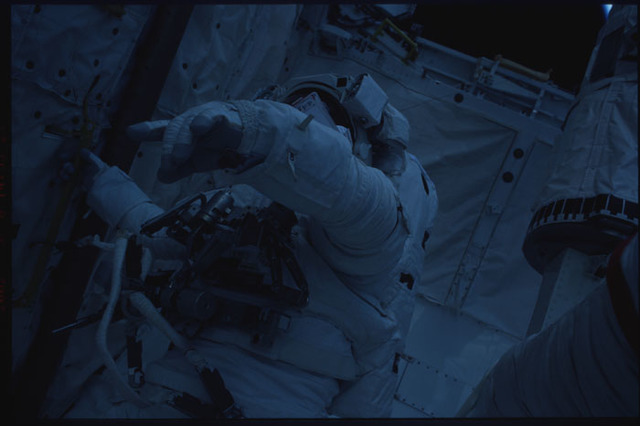 STS109-320-003 - STS-109 - EVA 5 - egress from airlock (underexposed)