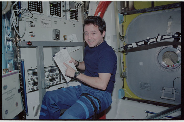 STS110-347-002 - STS-110 - Bursch looks over a checklist in the Airlock during STS-110's visit to the ISS