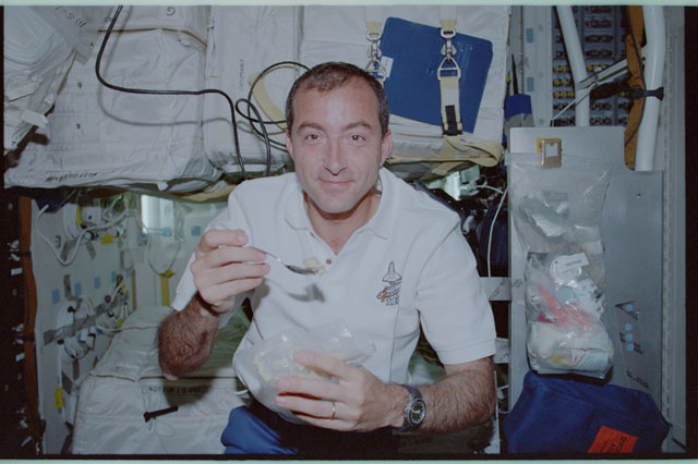 STS111-313-010 - STS-111 - Perrin enjoys a meal on Endeavour's MDK during STS-111 UF-2