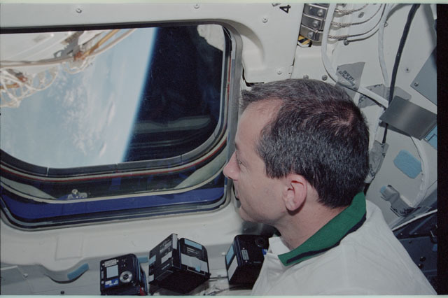 STS111-318-030 - STS-111 - Perrin peers through Endeavour's AFD window to view the Earth's limb during STS-111