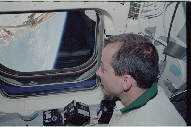 STS111-318-031 - STS-111 - Perrin peers through Endeavour's AFD window to view the Earth's limb during STS-111
