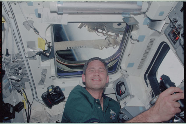 STS111-322-023 - STS-111 - Lockhart on Endeavour's AFD at RMS controls with SSRMS 'Canada' in window above him,  STS-111