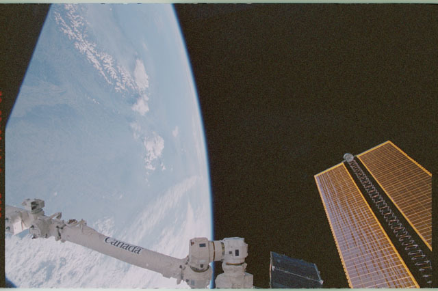 STS111-358-001 - STS-111 - SSRMS, Earth's limb, and tip of the port PV array as seen during STS-111 UF-2