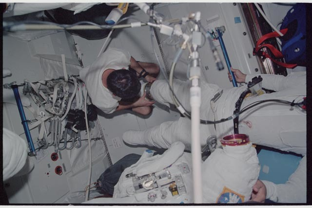 STS113-340-019 - STS-113 - Lockhart assists Herrington with EMU don during STS-113 EVA 2 prep in Quest A/L