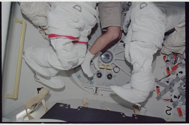 STS113-343-001 - STS-113 - STS-113 crewmember's feet & legs dangle between EMUs in the ODS
