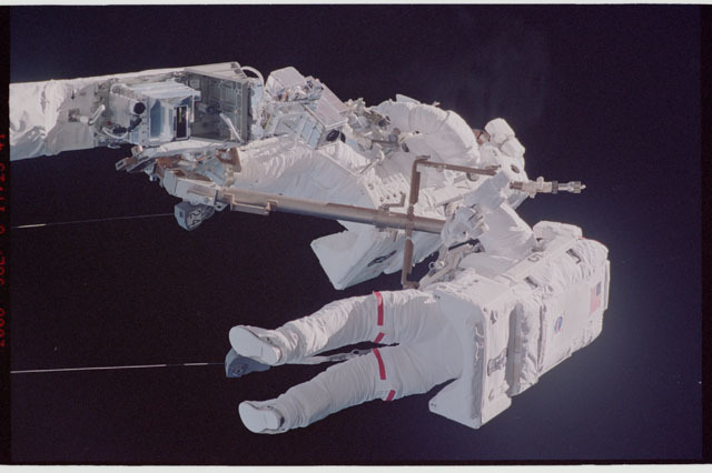 sts121-323-014 - STS-121 - Sellers and Fossum on the end of the OBSS during EVA1 on STS-121 / Expedition 13 joint operations
