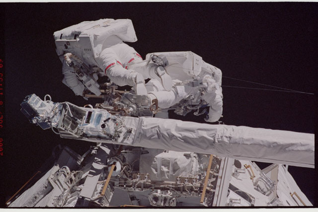 sts121-323-018 - STS-121 - Sellers and Fossum on the end of the OBSS positioned in front of the P1 Truss during EVA1 on STS-121 / Expedition 13 joint operations