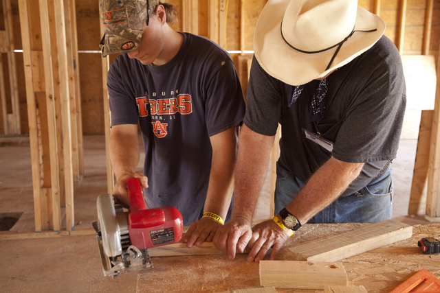 Tornado - Tuscaloosa, Ala. , August 2, 2011 -- Habitat volunteer Blake Maulden uses a radial saw to trim studs while assisted by his supervisor Lee Reynolds as Habitat for Humanity volunteers work in 100 degree heat to rebuild homes on 5th Street in Tuscaloosa after they were destroyed by a series of tornados that struck Alabama on April 27. FEMA supports the generosity and expertise of volunteer agencies (VOLAGS) like Habitat for Humanity. FEMA attempts to coordinate the agency's recovery efforts through its VOLAG liaison and VOLAG specialists. Photo by Christopher Mardorf /  FEMA.
