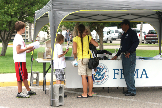 "Flooding - Bismarck, N. D. , August 6, 2011 -- FEMA Mitigation Liason Emiliano Flores, looks on as Community Relations Specialist Hilda Rodriguez speaks to interested community members at the FEMA information Booth at the base of the North Dakota State Capitol Building in Bismarck during a yearly festival called the ""Capitol a'Fair. "" FEMA utilized their booth at the fair to promote mitigation ideas to the community as well as providing information on programs available to those affected by the flood. Robert Kaufmann/FEMA"