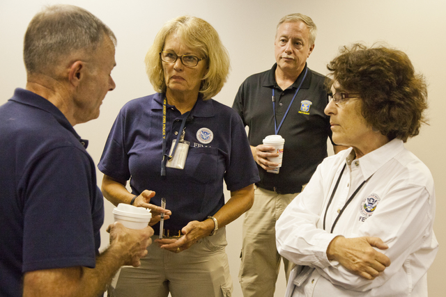 """Flooding ^ Hurricane/Tropical Storm - Neptune, N. J. , September 6, 2011 -- FEMA leadership prepares for a press conference hosted by New Jersey Governor Christopher James """"Chris"""" Christie at a FEMA Joint Field Office (JFO) in Neptune. William """"Bill"""" Vogel (l-r), FEMA Federal Coordinating Officer (FCO), speaks with Patricia Brach, JIC AEAO, Greg Sharkey, Lead Security Manager, and Phyllis Deroian, External Affairs Officer, before he speaks at Governor Christie's press conference to update the media and the public... Photo by Christopher Mardorf / FEMA."""