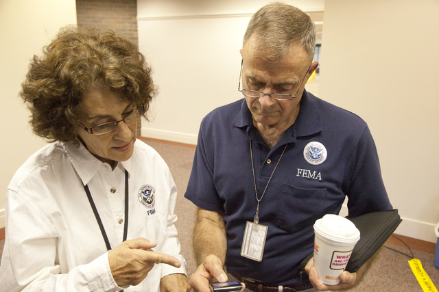 """Flooding ^ Hurricane/Tropical Storm - Neptune, N. J. , September 6, 2011 -- FEMA leadership prepares for a press conference hosted by New Jersey Governor Christopher James """"Chris"""" Christie at a FEMA Joint Field Office (JFO) in Neptune. William """"Bill"""" Vogel, FEMA Federal Coordinating Officer (FCO), confers with Phyllis Deroian, External Affairs Officer, before Mr. Vogel attends the press conference to update the media and the public about the ongoing efforts of FEMA to assist the state and local governments in their response to flooding and wind damage caused by Hurricane Irene on August 28. Photo by Christopher Mardorf / FEMA."""