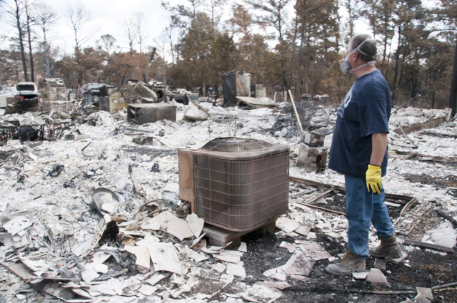 Fire - Bastrop, Texas, September 17, 2011 --A resident looks at the remains of his home after a fire destroyed it in Bastrop, TX. Photo by Patsy Lynch/FEMA