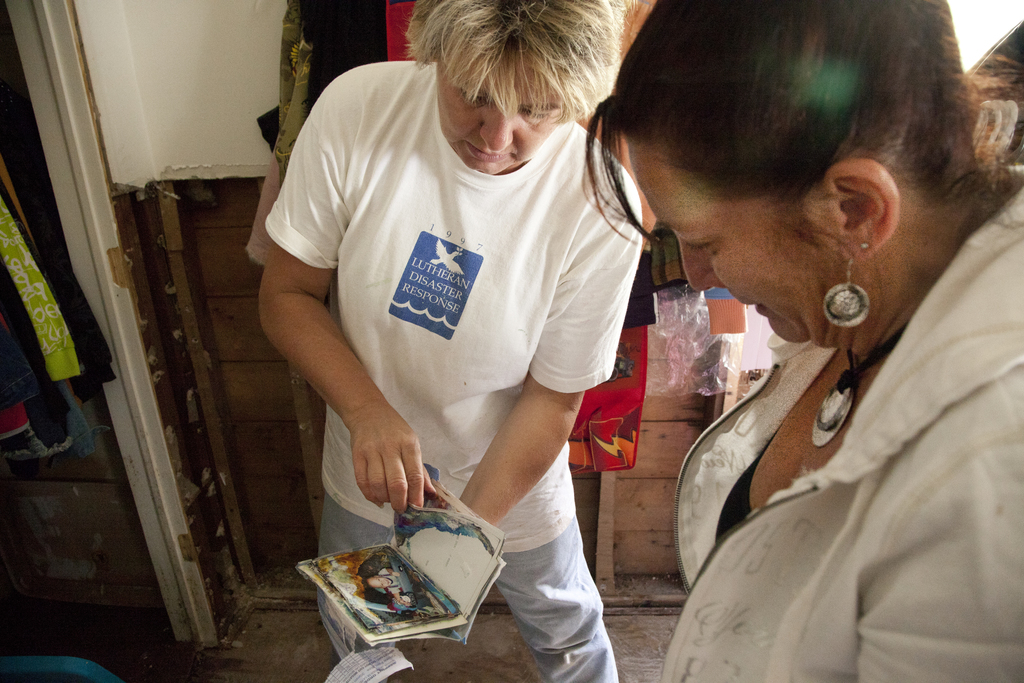 Flooding ^ Hurricane/Tropical Storm - Manville, N. J. , September 17, 2011 -- Cindy Zimmerman (left), a Faith Lutheran Church volunteer, shows a water-damaged photo album to disaster survivor Dawn Cohen in her recently flooded home. Volunteers from Faith Lutheran Church in Hillsborough, New Jersey, remove debris from the home of disaster survivors Dawn and David Cohen whose home in Manville suffered severe flooding damage caused by Hurricane Irene on August 28. FEMA works with and coordinates the generous activities of volunteer agencies like Lutheran Disaster Response when responding to disasters. Photo by Christopher Mardorf /  FEMA.