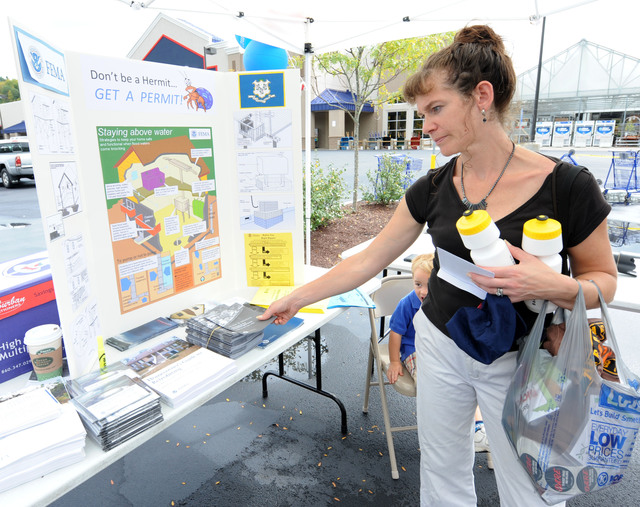 Hurricane/Tropical Storm - Torrington, Conn. , September 24, 2011 --Carol Lapointe of Winchester looks at information at a booth set up at a Family Day held at Lowe's. FEMA representatives handed out information about mitigation techniques to help prevent and mitigate future damage caused by storms and natural disasters.  Jocelyn Augustino/FEMA
