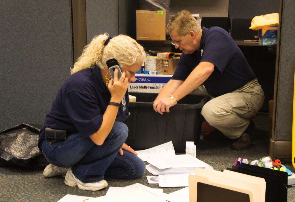 Hurricane/Tropical Storm - Jamaica, Long Island, NY, September 26, 2011 -- Eileen Lopez and Buz Boback sort files, paper, and other office supplies to get the DRC up an running on it's opening day.  The DRC, located in Jamaica, Long Island, New York services those in the area who had damage from Hurricane Irene.  Judith Grafe/FEMA Photo