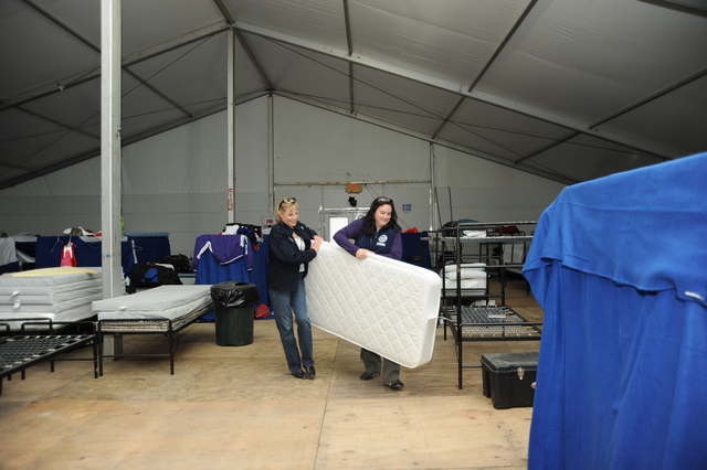 Flooding - Minot, N. D. , October 11, 2011 -- FEMA Region VIII Administrator Robin Finegan (left) moves a mattress at the Responder Base Camp in Minot, accompanied  FEMA External Affairs Executive Officer Megan Floyd. Finegan spent several nights at the camp meeting with the responders while in the Minot area addressing faith-based group concerns and viewing recovery efforts after the damage caused by June's Souris River flooding. Photo by Cynthia Hunter/ FEMA