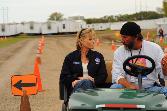 Flooding - Velva, N. D. , October 11, 2011 -- FEMA Region VIII Administrator Robin Finegan listens to Velva Staging Area Manager Linwood Gantt's concerns during a recent site visit. Finegan was in the Minot area meeting with faith-based groups and viewing recovery efforts after the damage caused by June's Souris River flooding. Photo by Cynthia Hunter/ FEMA