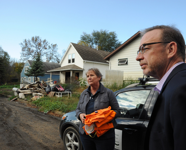 """Flooding - Minot, N. D. , October 12, 2011 -- David Myers, Director of the DHS Center for Faith-based and Neighborhood Partnerships, hears about recovery efforts with Rhonda Thompson, Ward County Coordinator for Lutheran Disaster Response, who is helping volunteers to clean and """"muck out"""" a flooded Minot home. Myers was in Minot meeting with faith-based groups and surveying the damage caused by June's Souris River flooding. Photo by Cynthia Hunter/ FEMA"""