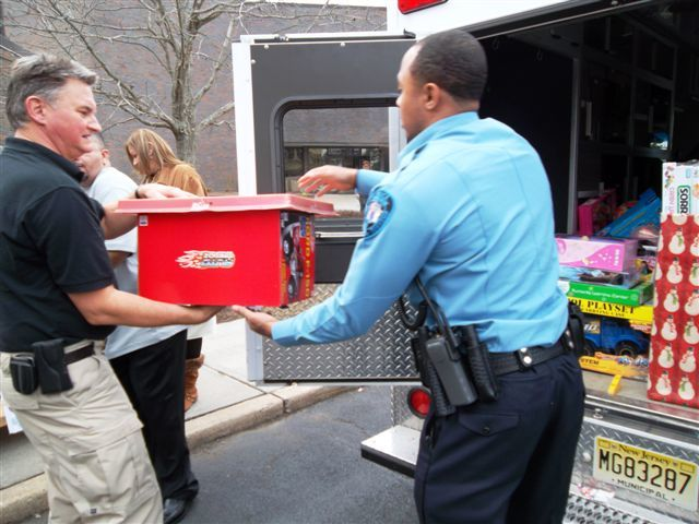 Hurricane/Tropical Storm - Neptune, N. J. , Dec. 15, 2011 -- FEMA's Anthony Innes (left), who helped coordinate the Toys for Tots campaign, loads toys into an emergency vehicle with Patrolman Mysonn Ledet, (right) of the Neptune Township Police Department. The toys will be distributed to needy families in the greater Neptune community. Photo by Phyllis Deroian/FEMA