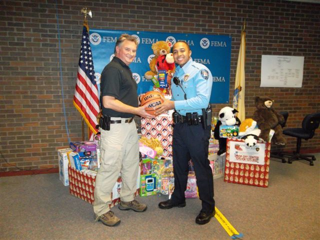 Hurricane/Tropical Storm - Neptune, N. J. , Dec. 15, 2011 -- Patrolman Mysonn Ledet, (right) of the Neptune Township Police Department, accepts a basketball from FEMA's Anthony Innes, who helped coordinate the Toys for Tots campaign to benefit needy families in the greater Neptune community. Photo by Phyllis Deroian/FEMA