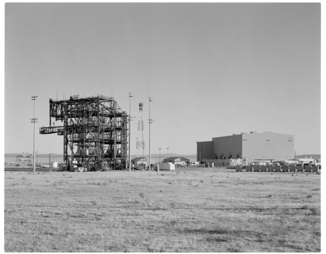 Establishing view, looking southeast, of NASA DFRC Mate-Demate Device (MDD), RF tower, stadium lights, and Shuttle Hangar (Building 4833) on right. Also visible on right: concrete weights for proof load tests
