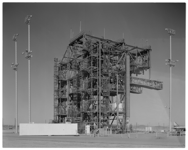 NASA DFRC Mate-Demate Device (MDD) full side view looking north, showing stadium lighting, South Personnel/Equipment hoist and port side Shuttle Access Platform (SAP) and counter-balance