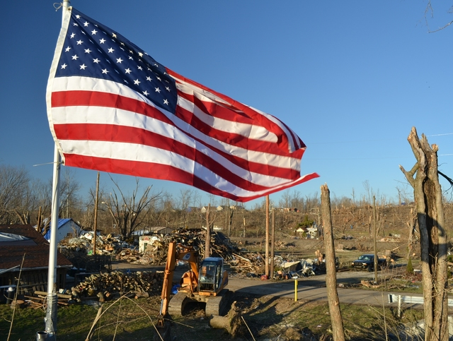 Tornado - Henryville, Ind. , March 8, 2012 -- The American Flag waves as a symbol of hope over the damaged homes and striped hillside after two tornadoes torn through the community of 1,900 residents in Southern Indiana on March 2.  President Obama issued a major disaster declaration on March 9, two days after the Joint Preliminary Damage Assessments were completed in six counties. Photo by Gene Romano/FEMA
