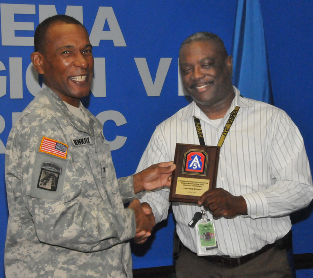 "Denton, Texas, May 21, 2012 -- Col. Bryan Newkirk, Defense Coordinating Officer for FEMA Region 6, presents a Plaque of Appreciation to ""Bullett"" Young, of FEMA Region 6 for his support of a Logistics conference in April. FEMA/Earl Armstrong"