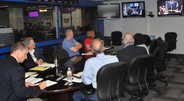 Denton, Texas, June 1, 2012 -- Acting Region 6 Administrator Tony Robinson (left) and several senior staff members participate in a Video-teleconference (VTC) on hurricane season 2012. Included in the screen on the left are FEMA Administrator Craig Fugate and DHS Secretary Janet Napolitano. FEMA/Earl Armstrong