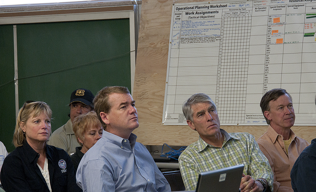 Fire - Fort Collins, Colo. , June 16, 2012 -- FEMA Region VIII Administrator Robin Finegan (3rd row, left), Sen. Mark Udall (2nd row, center) with Sen. Michael Bennet 2nd row, left) and Governor John Hickenlooper (2nd row, right) listen to a briefing at the High Park Fire Incident Command Post in Fort Collins on Sat. , June 16, 2012.  FEMA Photo/Cynthia Hunter