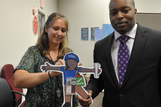 Washington, D. C. , June 27, 2012 --  J'son Tyson, Chief, Identity Credentialing Access Management Section (ICAM) and  Christina Dugan (standing), Security Specialist, ICAM place Flat Stella's badge around her. FEMA Photo
