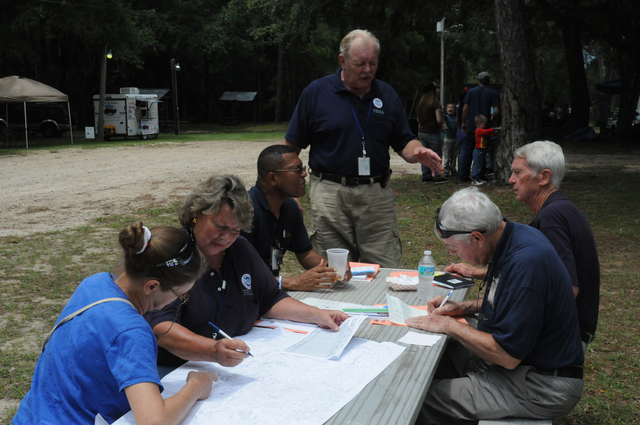 Flooding ^ Hurricane/Tropical Storm ^ Severe Storm - Sopchoppy, Fla. , July 4, 2012 -- As part of FEMA Community Relations (CR) outreach to Wakulla County storm survivors, CR Manager Duane Marusa provides information to CR Manager Serge Philippeaux, CR Specialists Charles Minerman, and Steve Huffstutler while CR Specialist Brenda Cheek gives FEMA Registration information at the local July 4th celebration.  FEMA is here in response to Tropical Storm Debby.  George Armstrong/FEMA