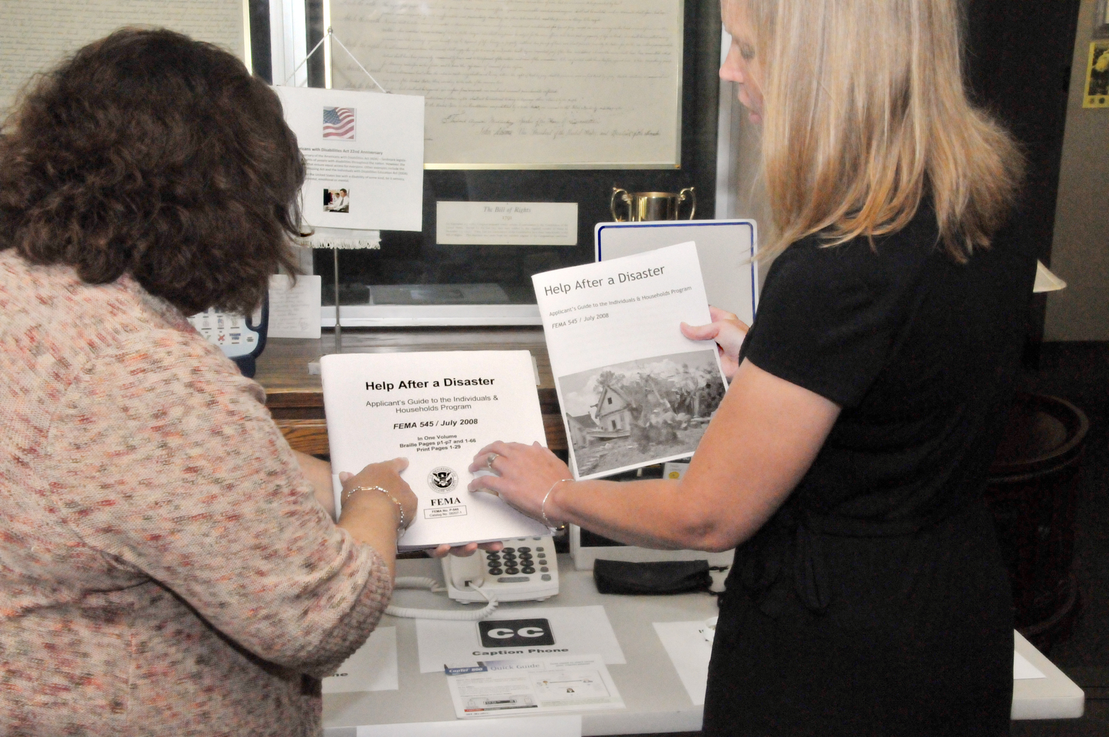 """Denton, Texas, July 26, 2012 -- Today is the 22nd Anniversary of the Americans with Disabilities Act (ADA). Norma Reyes (left) and Stephanie Moffett (right) of FEMA Region 6 look at two versions of """"Help After A Disaster. """" The one on the left--even though it has printing on it--is the Braille version. FEMA/Earl Armstrong"""