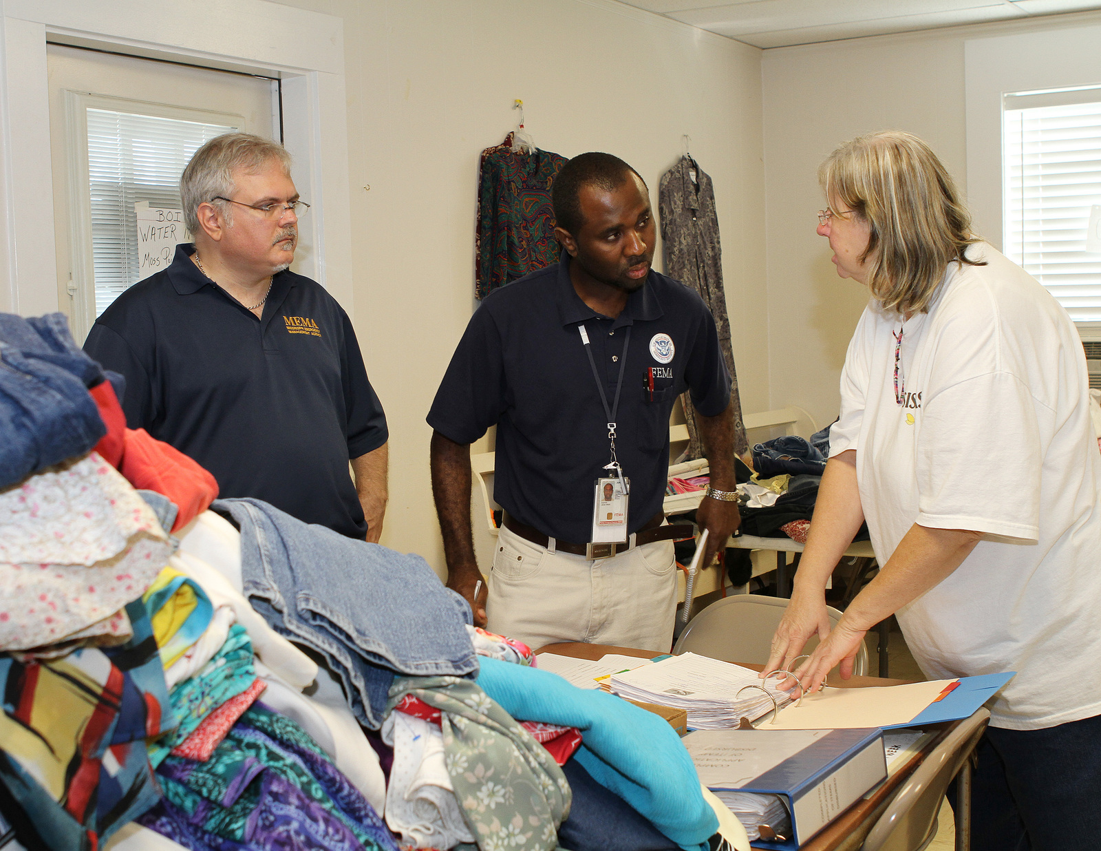 """Hurricane/Tropical Storm - Helena, Miss. , Sep. 12, 2012 -- FEMA Community Relations Specialist Jean Ones Austin, Mississippi Emergency Management Agency (MEMA) Specialist Eric Hambrick (L), speak with the president of the volunteer group """"Sisters"""" about their community outreach to support Hurricane Isaac disaster survivors with clothing, food and supplies.  FEMA and MEMA are working together to help survivors following Hurricane Isaac on August 28, 2012.  David Fine/FEMA"""