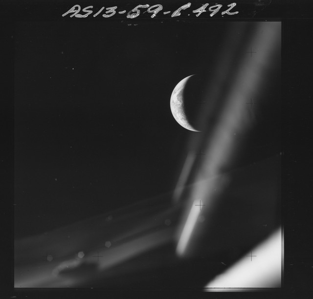 AS13-59-8492 - Apollo 13 - Apollo 13 Mission image  - Dark view of crescent Earth with Command Module (CM) window frame in view