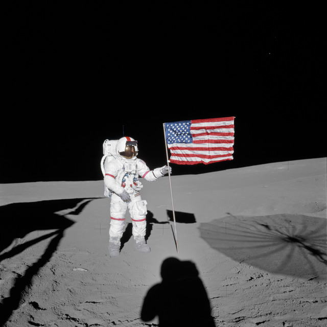 AS14-66-9232 - Apollo 14 - Apollo 14 Mission image - Astronaut Alan B. Shepard, Jr., commander of the Apollo 14 lunar landing mission, stands by the deployed United States flag on the lunar surface during the early moments of the first Extravehicular Activity (EVA-1) of the mission.