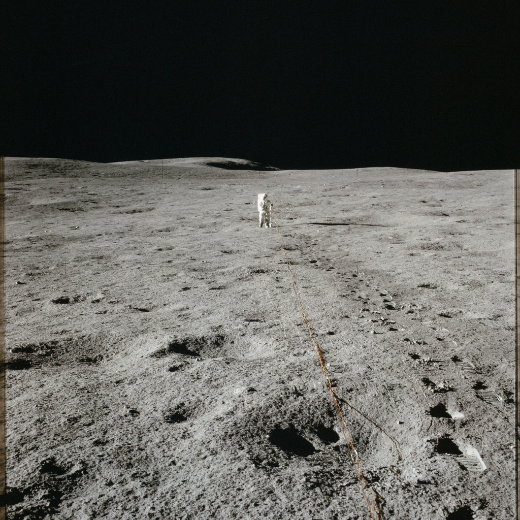 AS14-67-9374 - Apollo 14 - Apollo 14 Mission image - View to the south of LMP Shepard installing ASE equipment