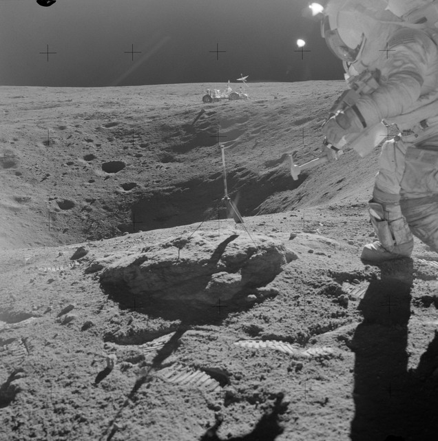 AS16-109-17804 - Apollo 16 - Apollo 16 Mission image - Astronaut John W. Young, commander of the Apollo 16 lunar landing mission, stands on the rim of Plum Crater while collecting lunar samples at Station 1 during the first Apollo 16 extravehicular activity (EVA-1) at the Descartes landing site