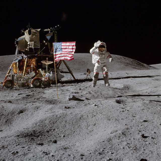 AS16-113-18339 - Apollo 16 - Apollo 16 Mission image - Astronaut John W. Young, commander of the Apollo 16 lunar landing mission, leaps from the lunar surface as he salutes the United States flag at the Descartes landing site during the first Apollo 16 extravehicular activity (EVA-1).