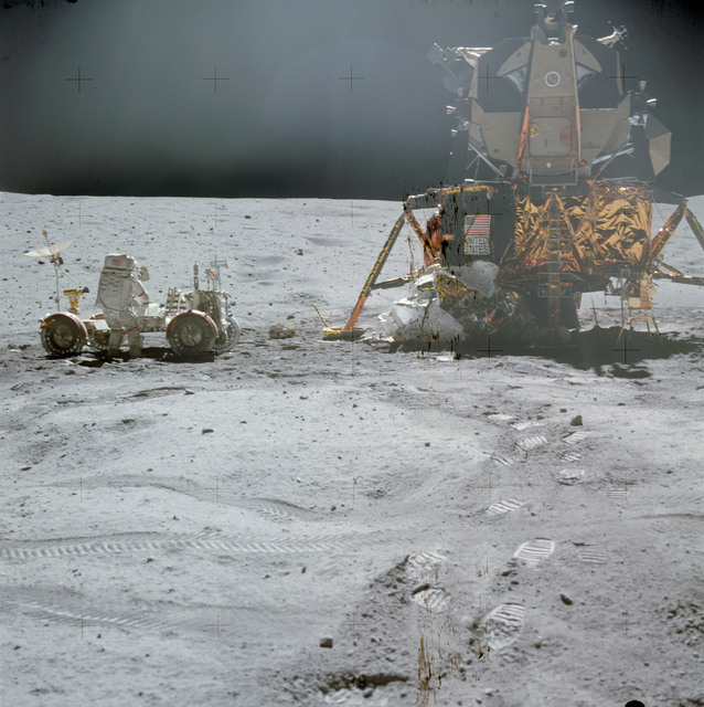 AS16-116-18578 - Apollo 16 - Apollo 16 Mission image - Astronaut John W. Young, commander of the Apollo 16 lunar landing mission, works at the Lunar Roving Vehicle (LRV) just prior to deployment of the Apollo Lunar Surface Experiments Package (ALSEP) during the first extravehicular activity (EVA-1) on April 21, 1972. Note the Ultraviolet (UV) Camera/Spectrometer to the right of the Lunar Module (LM) ladder.