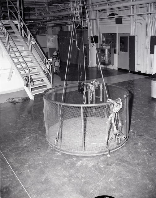 CAGE IN ZERO GRAVITY 0-G FACILITY TRANSPORTING MEN IN CHAMBER