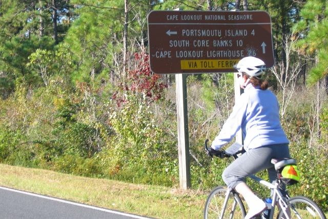 Outer Banks Scenic Byway - Biking past Directional Sign in Cape Lookout National Seashore